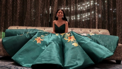 Young woman on a green gown smiles while sitting on a sofa.