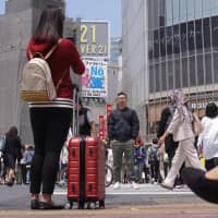 A woman takes a photo at Tokyo's famed Shibuya scramble crossing earlier this month. Many travelers end up sightseeing while dragging along their suitcases because it is often difficult to find an empty coin locker large enough to accommodate big pieces of luggage.