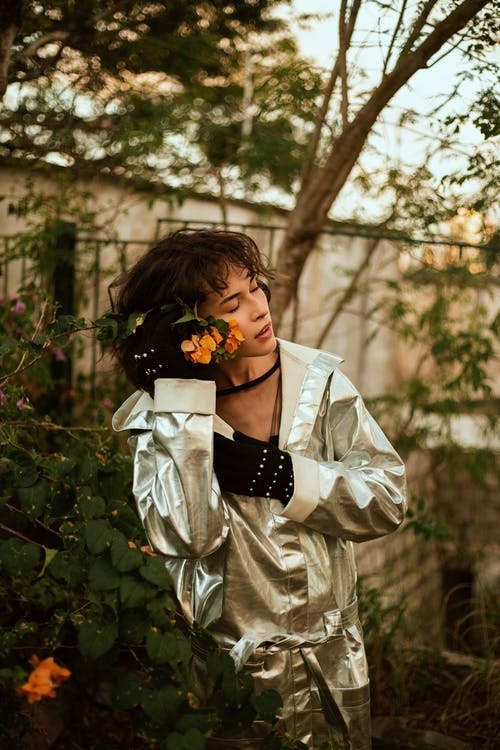 Woman in Silver Coat Holds Yellow Flowering Plant