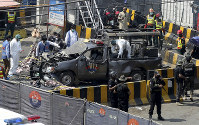 Pakistani security personnel surround a damaged police van in Lahore, Pakistan, on May 8, 2019. (AP Photo/K.M. Chaudary)