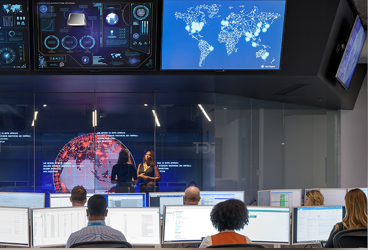 Photograph of people seated in front of rows of large monitors on their desk and mounted high on the wall in the Microsoft Cyber Defense Operations Center. In an adjacent room with glass walls, two people are talking in front of a giant monitor displaying information from around the globe.