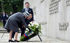 Queen Elizabeth and the Duke of Edinburgh lay a wreath in front of the inscription wall