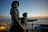 Statue of Annie Moore and her brothers on the quayside in Cobh, Ireland.