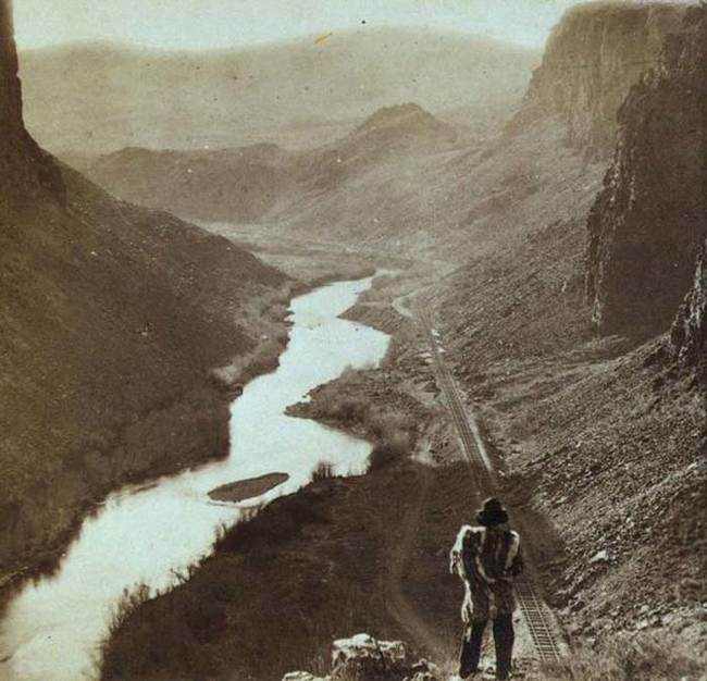 18 - A Native American observers the completed Transcontinental railroad