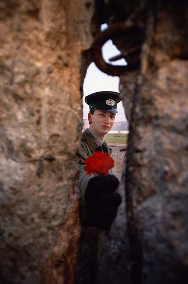 2 - 1989 - East German soldier passing a flower through the Berlin Wall before it was torn down