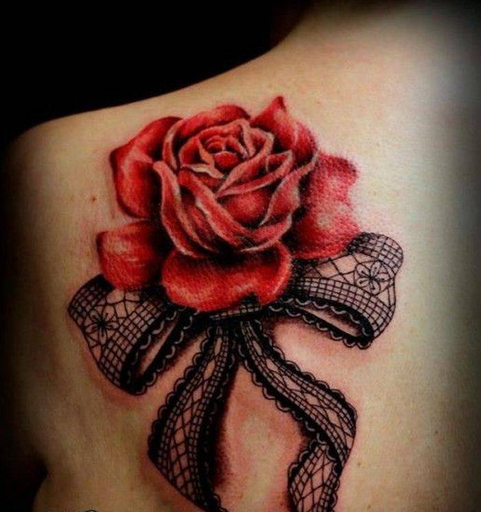 Tattoo on the shoulder blade of the girl - rose and bow