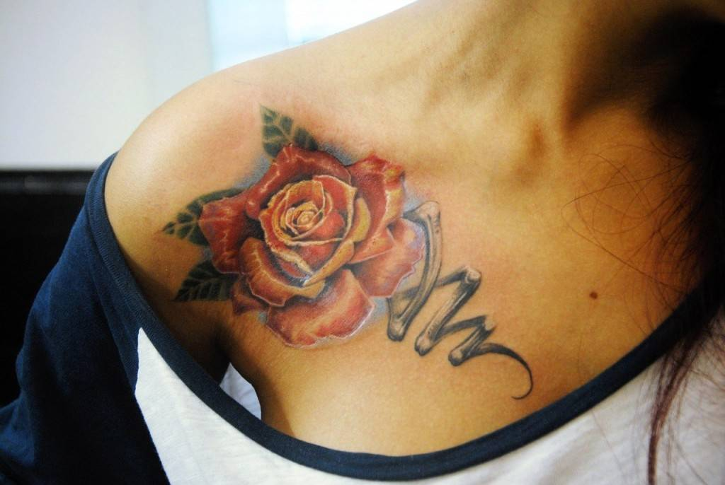 Tattoo on the clavicle at the girl - red rose