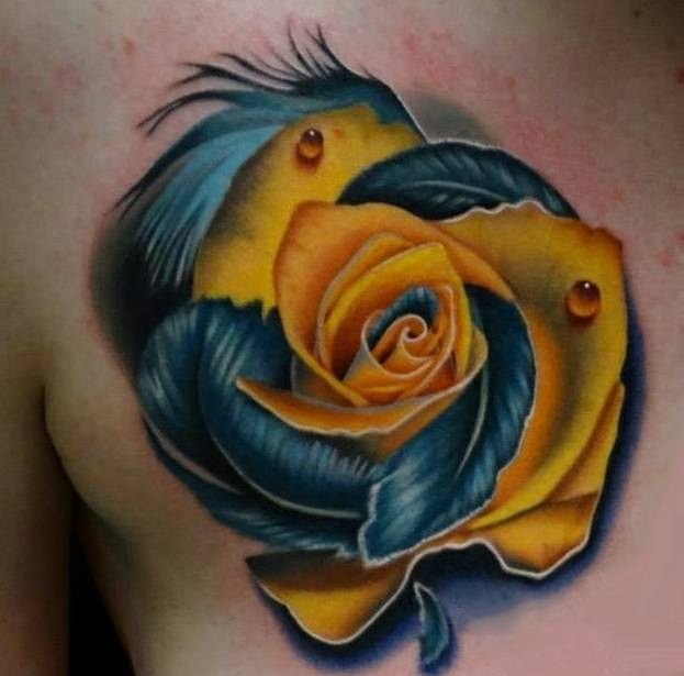 Tattoo on the chest of the girl - yellow rose with feathers