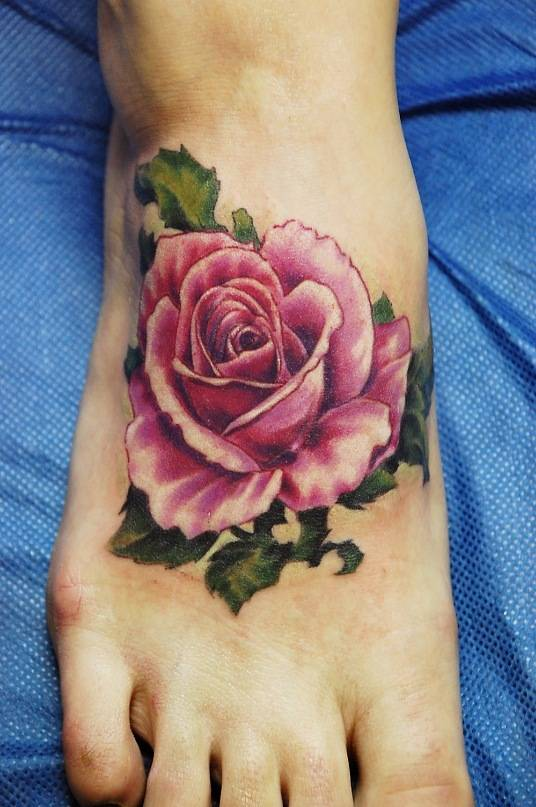Tattoo on the foot of the girl - pink rose