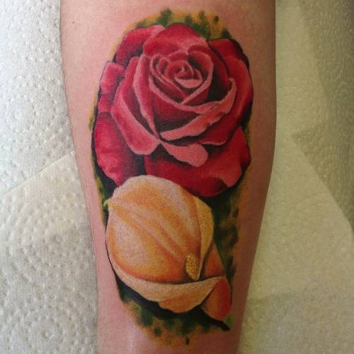 Tattoo on the forearm of the girl - rose and calla