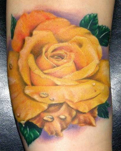 Tattoo on the arm of the girl - yellow rose