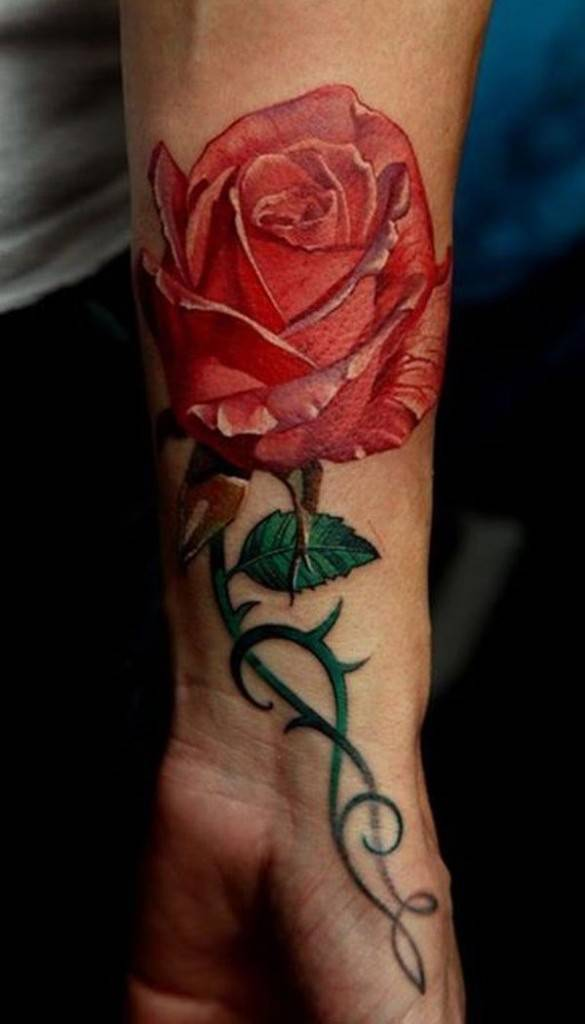 Tattoo on the wrist of the girl - red rose with leaves and thorns