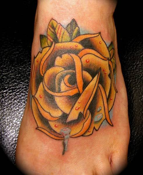 Tattoo on the foot of the girl - yellow rose