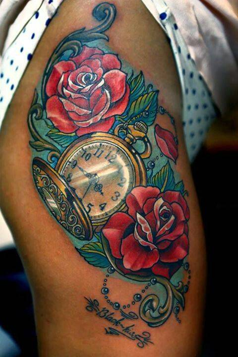 Tattoo on the hips of the girl - red roses and clock
