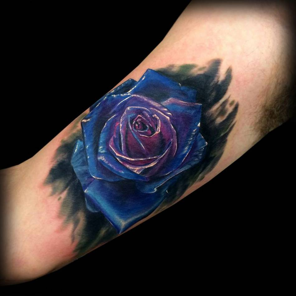 Tattoo on the biceps of a man - the blue rose