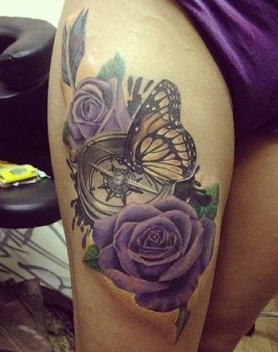 Tattoo on the hips of the girl - purple rose, compass and butterfly