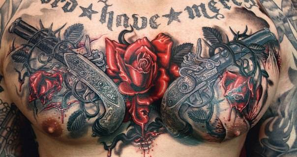 Tattoo on chest men - Red roses, barbed wire and two pistols