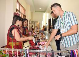 Byron Hartzler (front right), one of the panelists and founder of Myanmar Adventure Outfitters, browses an exhibit selling traditional clothing of the Gheba ethnic people. Photo - Supplied