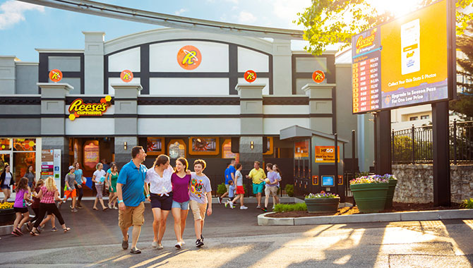 family of 4 walking away arm-in-arm from the new Reese Cupfusion Attraction