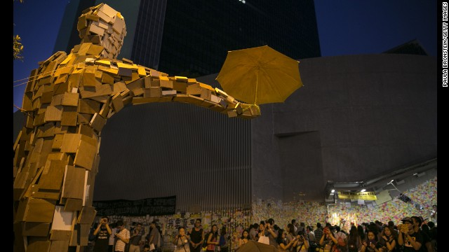 """People gather beneath the statue """"Umbrella Man,"""" by the Hong Kong artist known as Milk, which has become a symbol at the protest site, on Saturday, October 11, in Hong Kong."""
