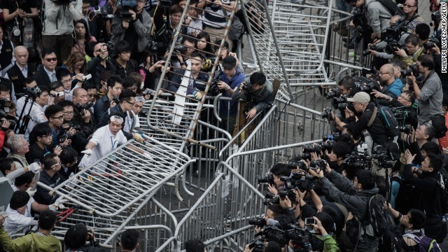 Security staff members remove a barricade outside the CITIC tower near a protest site in the Admiralty district of Hong Kong on Tuesday, November 18.