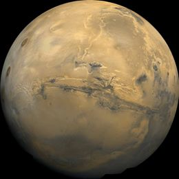 view of Mars from space; Valles Marineris is visible as a horizontal-like line toward the center of the light brown planet
