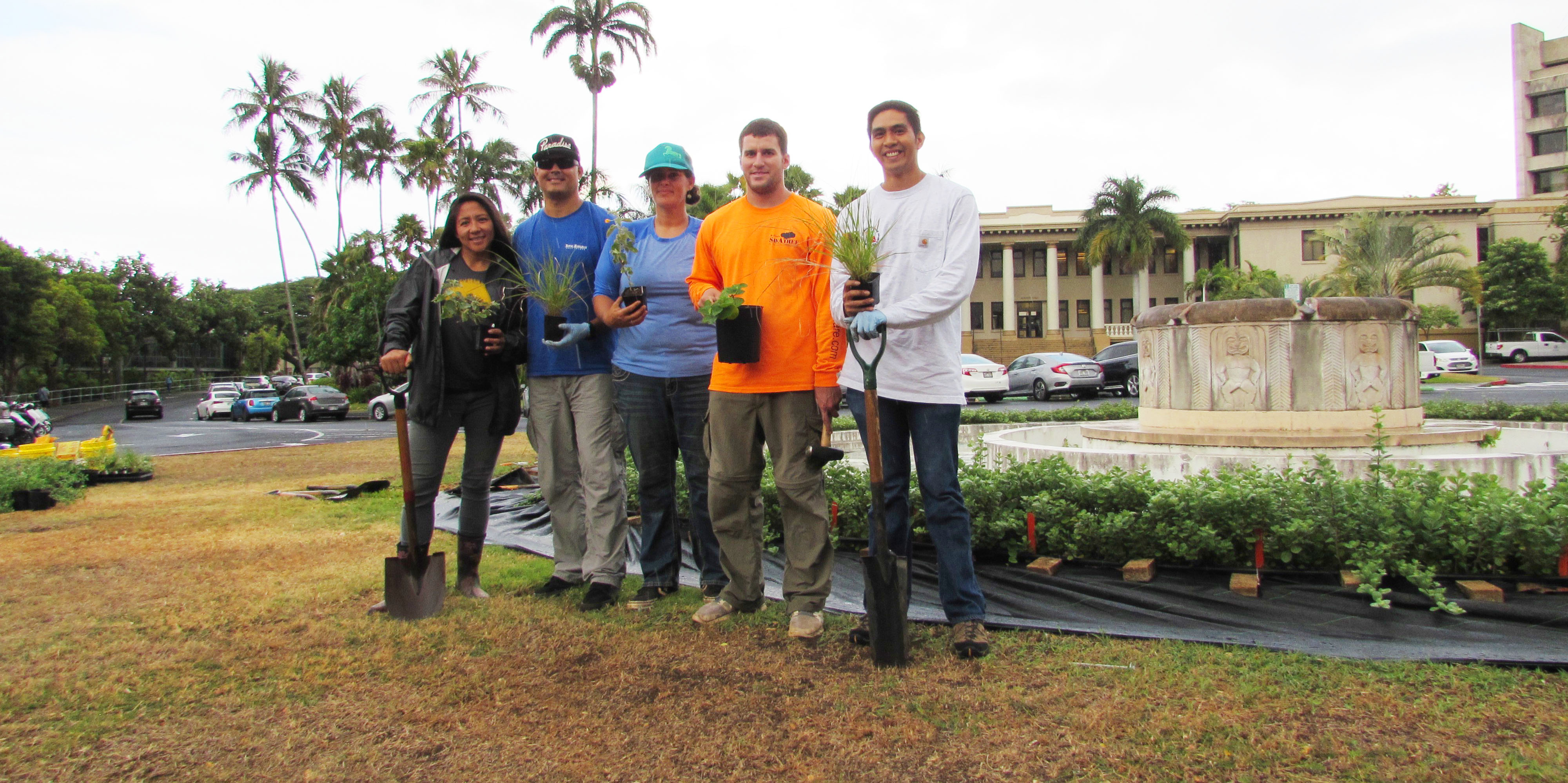Landscaping team holding potted plants in front of Hawaii Hall at Manoa.