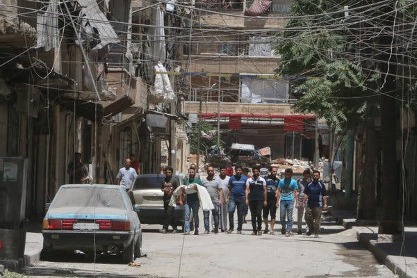 A man carried the body of his young son, who he said had been killed by an airstrike, through the streets of a rebel-held neighborhood of Aleppo, Syria, on Tuesday.