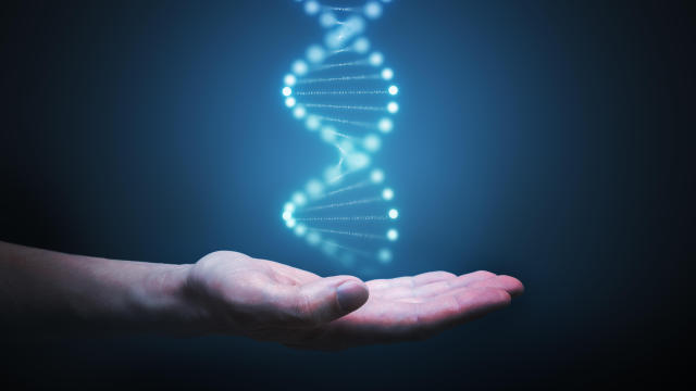 DNA and genetics research concept. Hand is holding glowing DNA molecule in hand.