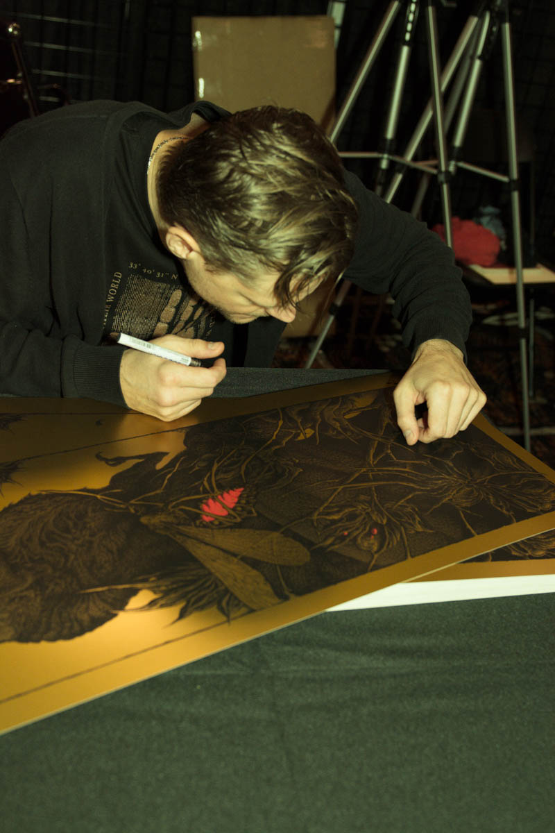 Aaron Horkey signing and numbering his 'Inclusion' prints in The Vacvvm booth | photo by Holly Burnham