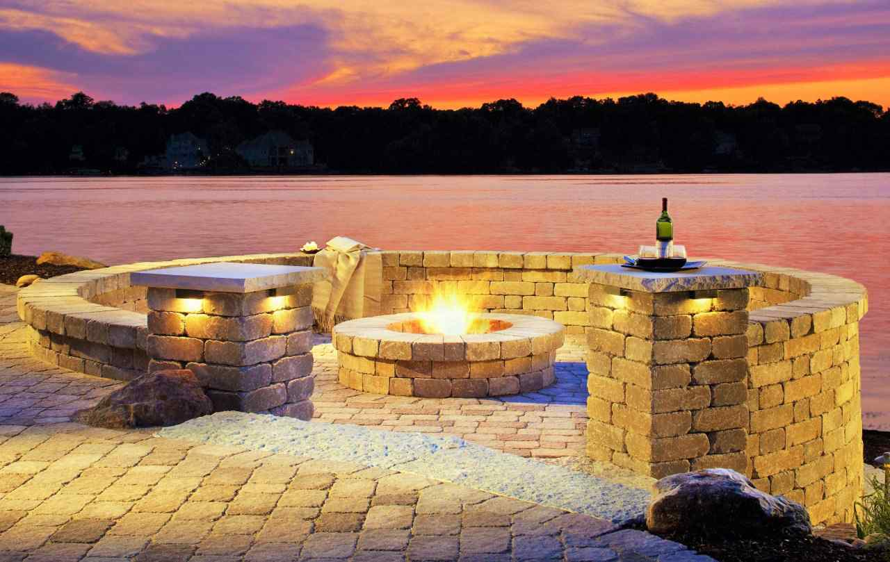 fire pit on patio paved in cobblestone with retaining wall