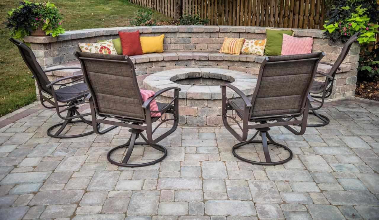 round fire pit on random edge paved patio with seating and back rest