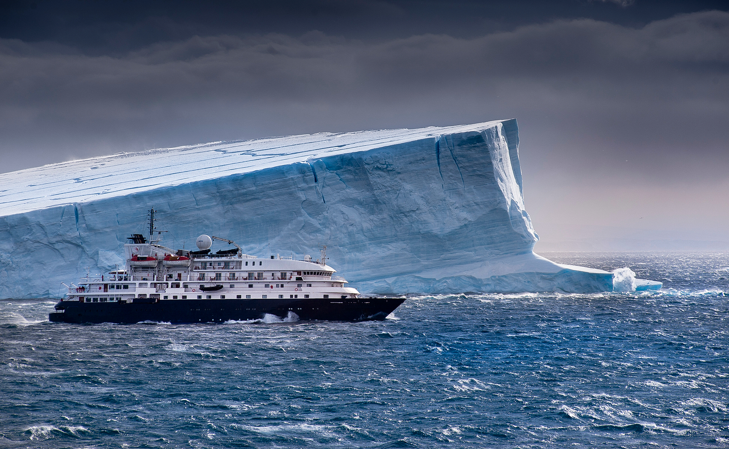 Cruise Ship in front of Iceberg in Antarctica