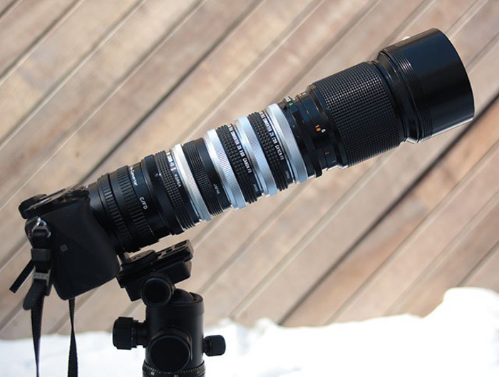 A teleconverter attached to a DSLR camera on a tripod