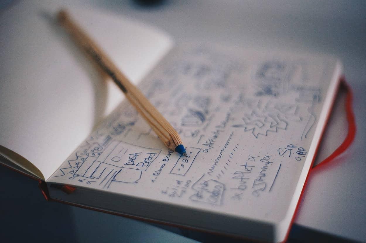 Foto eines aufgeschlagenen Notizbuches mit einem Bleistift, in dem gezeichnete Screendesigns & und unterschiedliche Konzepte zu sehen sind.