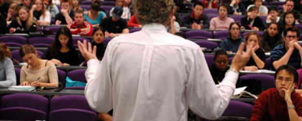 Back view of male prof lecturing to large class in lecture hall, many students