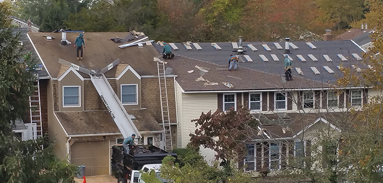 roofers using a dumpster