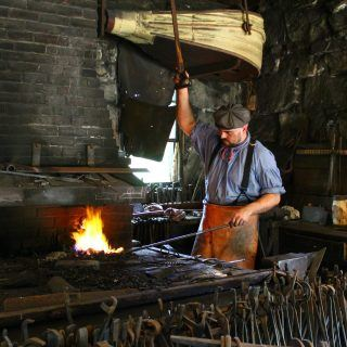 A costumed historian works the bellows in the Blacksmith Shop