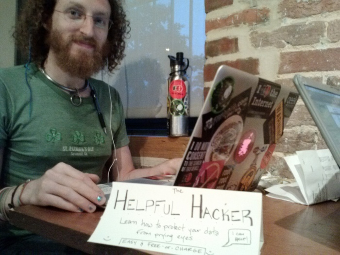 """Photograph of maymay as 'The Helpful Hacker' sitting in a café with a sign on the table that reads, """"The Helpful Hacker: Learn how to protect your data from prying eyes. Easy & Free-of-Charge. I can help!"""" :)"""