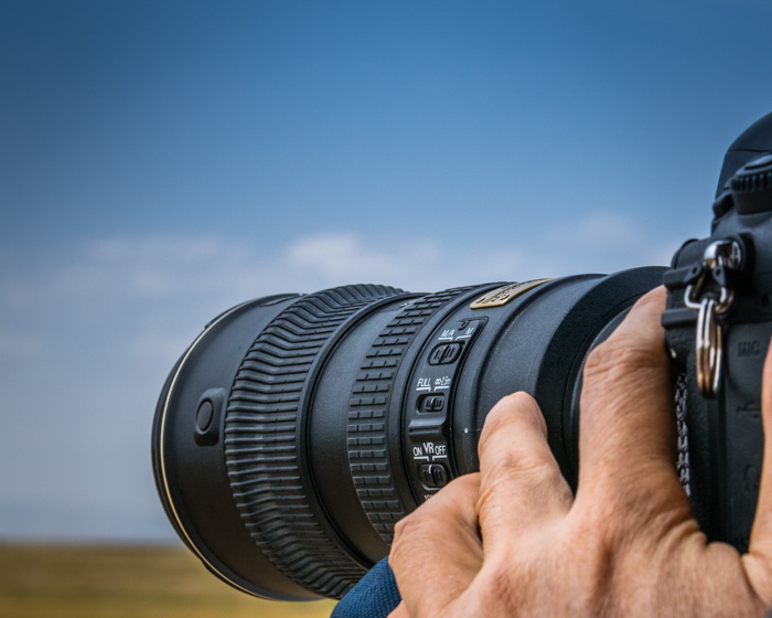 A close up of a photographer shooting a landscape with a dslr - Nikon to Canon lens adapter guide