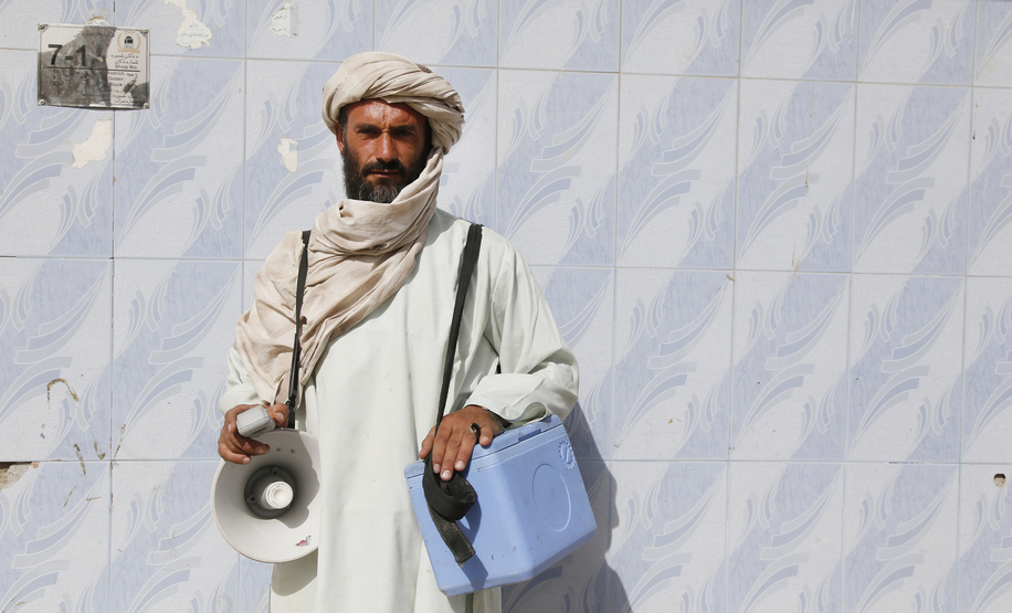 Polio vaccination campaign in Afghanistan.  A vaccinator carrying vaccine carrier and a loudspeaker poses for a picture in the field as they go mouth by mouth, house by house in every street to vaccine children under five years old.