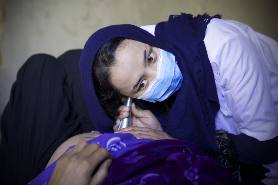 Mobile Clinic Afghanistan.  Shakila midwife listens to the heartbeat of a pregnant woman at the mobile clinic organized by WHO at the Garm Abak of Waras district in Bamiyan, Afghanistan.