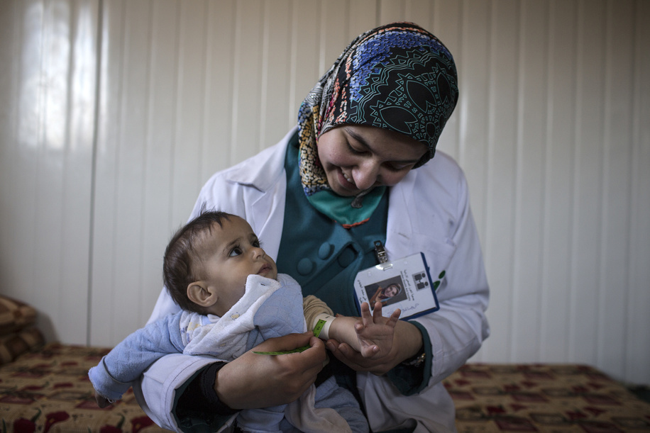 Bushra, a healthcare worker with the Jordan Health Aid Society (JHAS) performs mid-arm circumference measurements on a baby boy in the Zaatari refugee camp. In addition to running health education programmes for children and adults at the camp, JHAS teams monitor Noncommunicable Diseases (NCD) cases with clinic and home medical check ups. During such home visits, the local ngo staff examine patients' overall health, nutritional practice, insulin injection technique, and insulin storage conditions. Keeping the insulin cool at the Zaatari refugee camp with limited electricity access can be difficult, especially during the hot summer months. Since Zaatari opened in July 2012 to host Syrians fleeing the violence in the ongoing Syrian Civil War, it has become the world's largest camp for Syrian refugees.  Illustrations about diabetes in Jordan