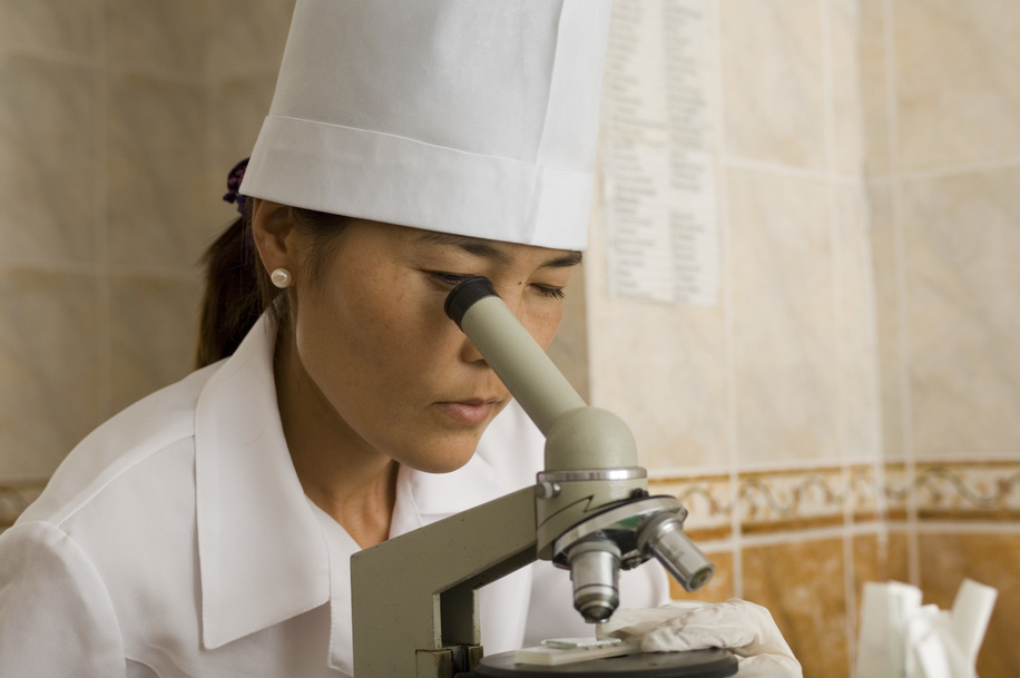 Primary health care in a Health Care Centre, some 40KM from Almaty (Kazakhstan).  A health worker looks through a microscope.