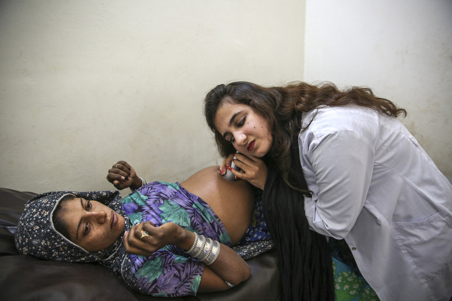 Dr Pooja, Somli a pregnant woman using a traditional fetal stethoscope during a routine antenatal examination in basic health unit Akora II, Nowshera District, Khyber Pakhtunkhwa province, Pakistan. Photographer: Asad Zaidi