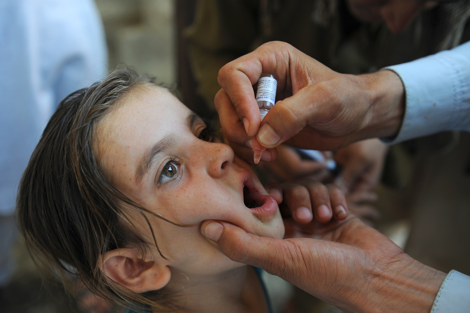 Polio vaccination campaign in Afghanistan.  Afghan permanent transit team vaccinator gives drops of polio vaccine for the children who are in the move as the first day of Polio campaign starts in Asadabad.