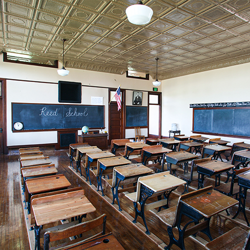 Inside the Reed School classroom, with vintage desks and a chalkboard
