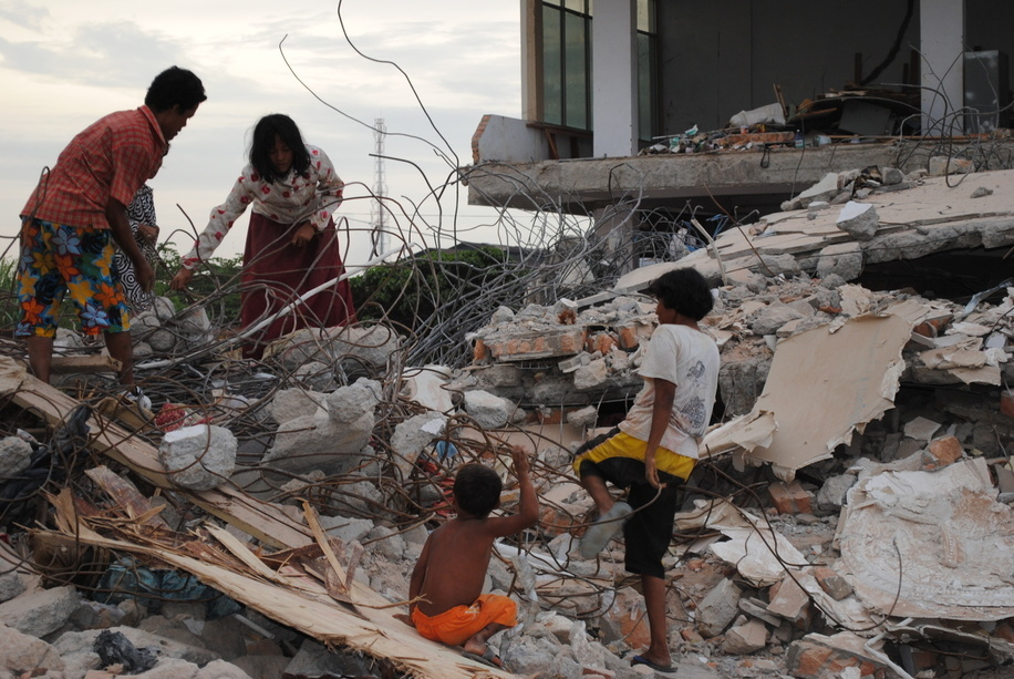 Earthquake in Sumatra, Indonesia   Feature on damage and destruction to infrastructure.  A family searching the rubble of a building damaged by the earthquake in Indonesia.