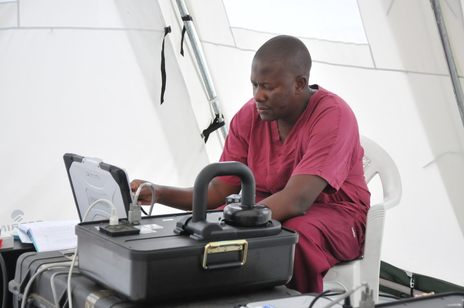 WHO and partner's response to Ebola virus disease (EVD) outbreak in Liberia.  Field mobile laboratory near ELWA 3 treatment facility is supported by CDC and WHO GOARN (Global Outbreak Alert and Response Network).  CDC staff monitors test results on a computer.