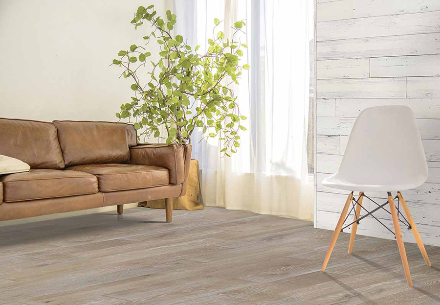 A modern living room with a 2020 theme that incorporates a brown leather couch and a white chair on engineered wood floors.